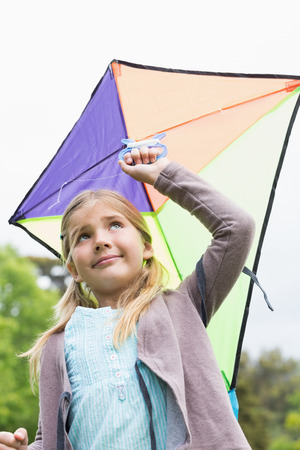 Low angle view of a cute young girl with a kite standing outdoors photo
