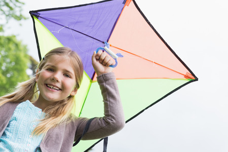 kite flying: Portrait of a cute young girl with a kite standing outdoors