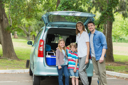 Portrait of a happy family of four by car trunk while on picnic photo