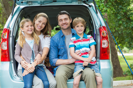 Portrait of a happy family of four sitting in car trunk while on picnic photo