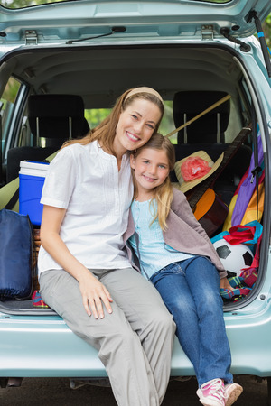 Portrait of a smiling mother and daughter sitting in car trunk while on picnic photo