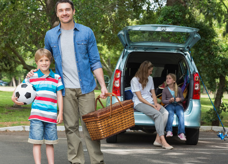 Portrait of father and son with picnic basket while mother and daughter sitting in car trunk photo