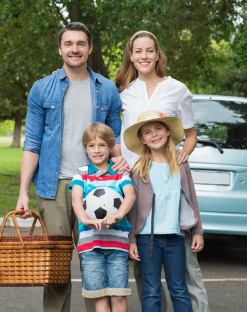 Portrait of a happy family of four with picnic basket photo
