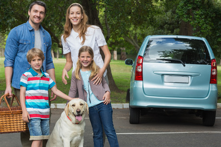 family outing: Portrait of a happy family of four with car at picnic