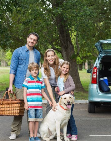 domestic car: Portrait of a happy family of four with car at picnic