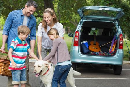 familia viaje: Retrato de una familia feliz de cuatro con su perro mascota en la comida campestre