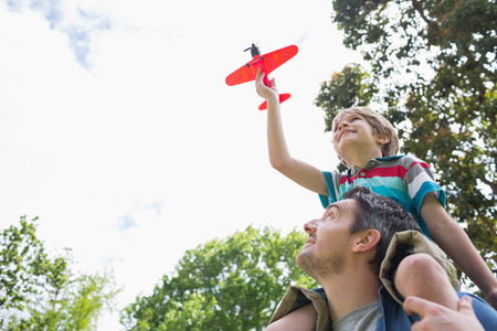 model airplane: Low angle view of a boy with toy aeroplane sitting on fathers shoulders at the park
