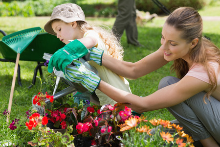 watering plants: Side view of a mother and daughter watering plants at the garden Stock Photo