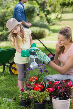 regando plantas: Madre con plantas de riego de la hija en el jard�n