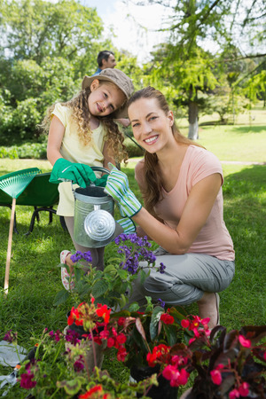 watering plants: Portrait of mother with daughter watering plants at the garden