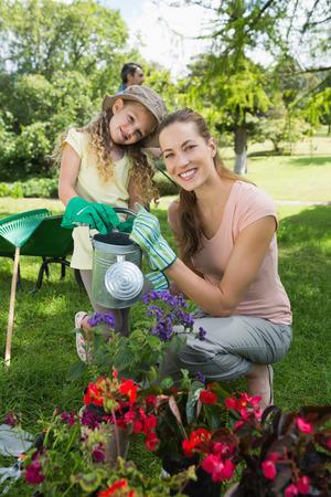 regando plantas: Retrato de la madre con la hija regar las plantas en el jard�n