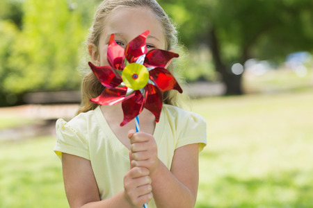 Close-up portrait of cute girl holding pinwheel at the park photo