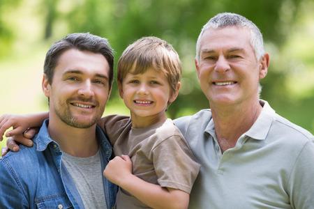 abuelo: Padre del abuelo y del hijo sonriendo contra el fondo borroso en el parque