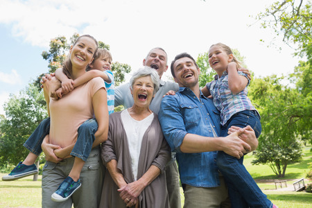 family relationships: Portrait of cheerful extended family standing at the park Stock Photo