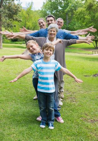 Portrait d'une famille élargie heureux debout dans la rangée avec les bras tendus dans le parc