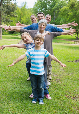 Portrait of a happy extended family standing in row with arms outstretched at the park