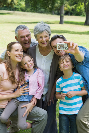 Man taking picture of his cheerful extended family at the park photo