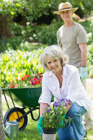 Portrait of a smiling mature woman engaged in gardening with man in background photo