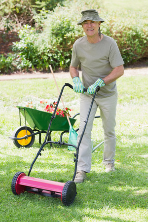 Full length portrait of a smiling man mowing the lawn photo