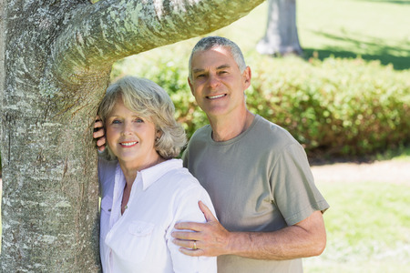 Portrait of a smiling mature couple besides a tree at the park photo