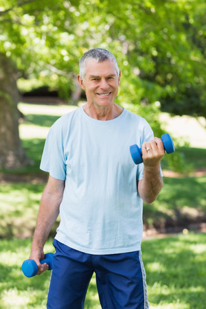 Portrait of a smiling mature man exercising with dumbbells at the park photo