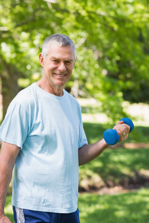 Portrait of a smiling mature man exercising with dumbbell at the park photo