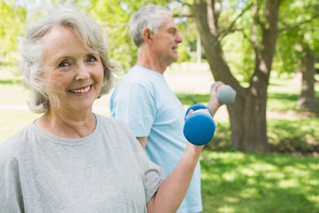 weight training: Portrait of a mature couple using dumbbells at the park