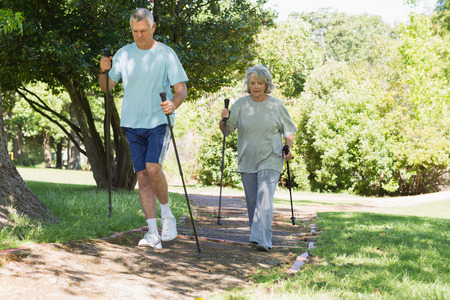 Full length of a mature couple Nordic walking on pathway in the park photo