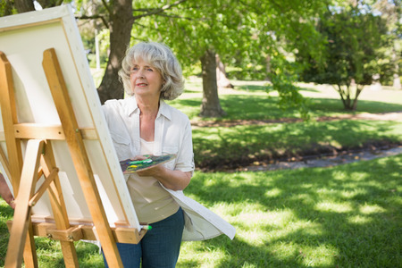 mature woman: Mature woman painting on canvas in the park