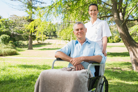 Woman with her mature father sitting in wheel chair at the park Stock Photo