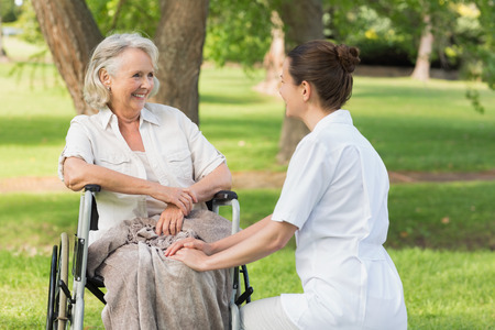 mother       care: Portrait of a woman with her mature mother sitting in wheel chair at the park Stock Photo