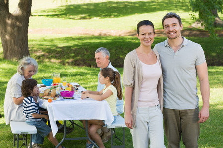 Portrait of a couple with family having lunch in background at the lawn photo