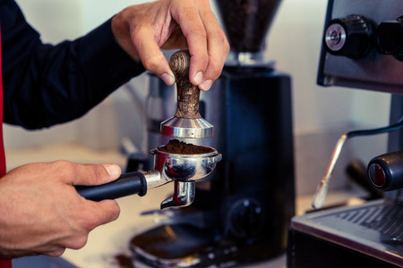 coffee grounds: Barista pressing fresh coffee grounds in a cafe