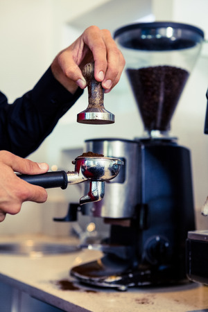 Barista pressing down fresh coffee grounds in a cafe photo