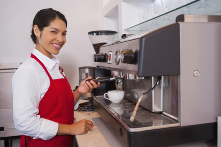 Pretty barista making coffee smiling at camera in a cafe photo