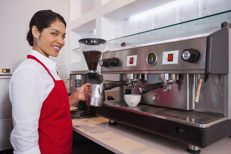 Pretty barista steaming jug of milk smiling at camera in a cafe photo
