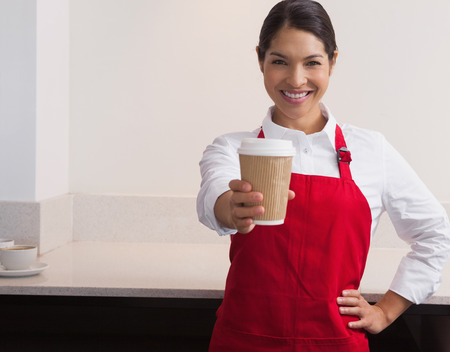 Pretty young barista offering cup of coffee to go smiling at camera in a cafe photo