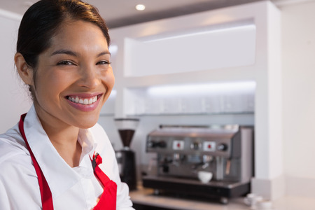Pretty barista smiling at camera in a cafe photo
