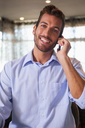 after to work: Hombre de negocios feliz hablando por tel�fono despu�s del trabajo en un bar