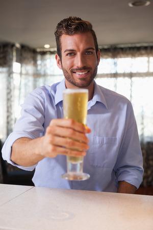 after to work: Feliz empresario elevar el vaso de cerveza a la c�mara despu�s del trabajo en un bar