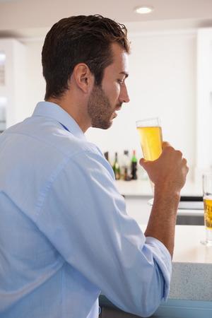 after to work: Cristal Apuesto hombre de negocios de beber de cerveza despu�s del trabajo en un bar Foto de archivo