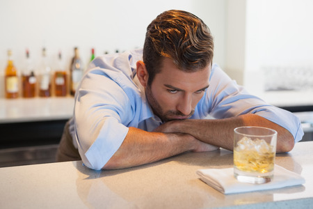 after work: Drunk businessman looking at his whiskey glass after work at the local bar Stock Photo