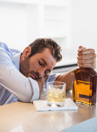 slumped: Drunk businessman clutching whiskey bottle asleep at the local bar Stock Photo