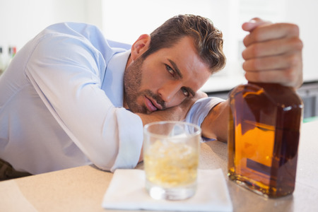 slumped: Drunk businessman clutching whiskey bottle looking at camera at the local bar