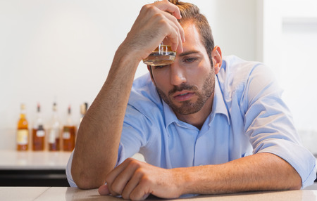 slumped: Drunk businessman clutching whiskey glass to head at the local bar