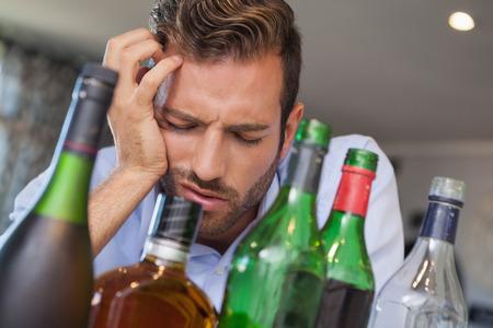 slumped: Drunk businessman slumped beside many spirit bottles at the local bar