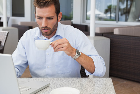 Concentrating businessman working with laptop drinking coffee in patio of restaurant photo