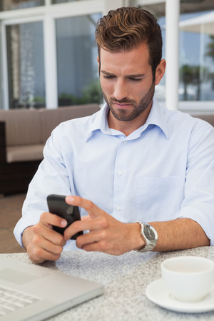Frowning businessman sending a text at table in patio of restaurant photo