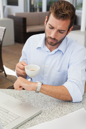 Frowning young businessman checking time holding coffee cup in patio of restaurant photo