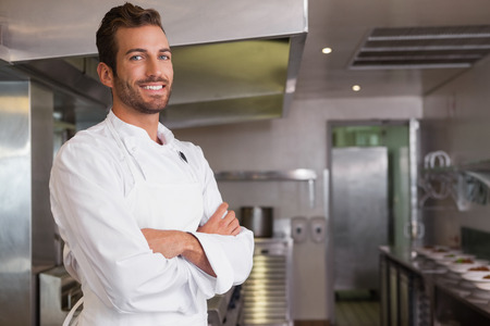Smiling young chef standing with arms crossed in a commercial kitchen Stock Photo